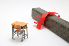 Study desk and diploma with a red ribbon on white background. Royalty Free Stock Image