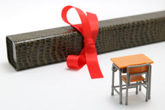 Study desk and diploma with a red ribbon on white background. Stock Image