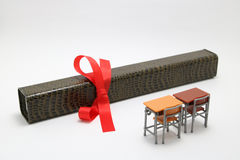 Study desks and diploma with a red ribbon on white background. Stock Photo