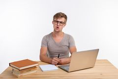 Study, education, people concept - student funny man doing exercises in netbook, looking surprised royalty free stock images