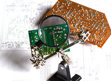 The study of the electrical board with a magnifying glass Royalty Free Stock Photos