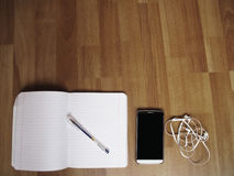 Study with fun and music. A mobile phone, headphones, copybook and a pen royalty free stock photography