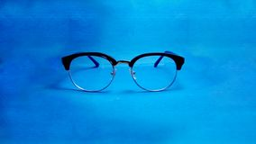 Study glasses on blue background royalty free stock images