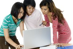 Study Group. Three asian students study at a desk with folder and laptop royalty free stock images