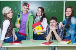 Study group in classroom. Portrait of six teens in classroom background green board Royalty Free Stock Photos