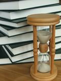 Study hard in no time. A lot of books with an hourglass, study hard in no time Royalty Free Stock Photos