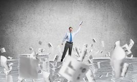 Study hard to become successful businessman. Businessman keeping hand with book up while standing among flying documents with grey background. Mixed media Royalty Free Stock Photos