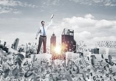 Study hard to become successful businessman. Businessman keeping hand with book up while standing among flying letters with cityscape and sunlight on background Royalty Free Stock Photo