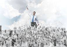 Study hard to become successful businessman. Businessman keeping hand with book up while standing among flying letters with cloudly skyscape on background Stock Photography