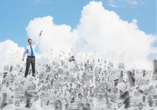 Study hard to become successful businessman. Businessman keeping hand with book up while standing among flying letters with cloudly skyscape on background Stock Image