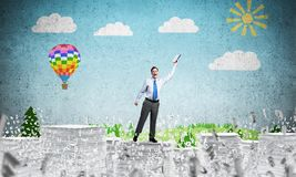 Study hard to become successful businessman. Businessman keeping hand with book up while standing among flying letters with drawn landscape on background. Mixed Stock Images
