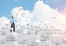Study hard to become successful businessman. Businessman keeping hand with book up while standing among flying paper planes with cloudly skyscape on background Royalty Free Stock Photo