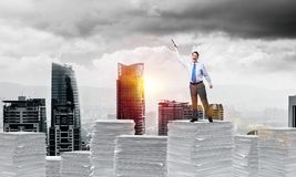 Study hard to become successful businessman. Businessman keeping hand with book up while standing on pile of paper documents with cityscape and sunlight on Royalty Free Stock Photography