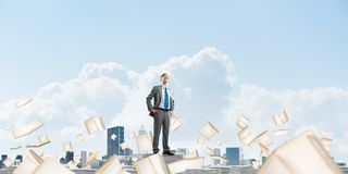 Study hard to become successful businessman. Confident businessman in suit standing on pile of documents among flying books with cloudly sky on background Royalty Free Stock Image
