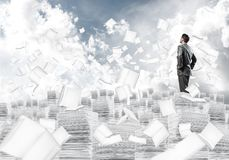 Study hard to become successful businessman. Confident businessman in suit standing on pile of documents among flying books with cloudly sky on background Stock Image