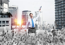 Study hard to become successful businessman. Businessman keeping hand with book up while standing among flying letters with cityscape and sunlight on background Stock Image