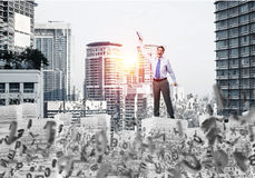 Study hard to become successful businessman. Businessman keeping hand with book up while standing among flying letters with cityscape and sunlight on background Stock Photo