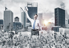 Study hard to become successful businessman. Businessman keeping hand with book up while standing among flying letters with cityscape and sunlight on background Stock Photos