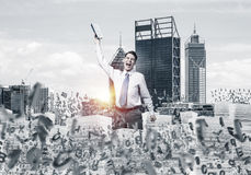 Study hard to become successful businessman. Businessman keeping hand with book up while standing among flying letters with cityscape and sunlight on background Stock Images