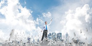 Study hard to become successful businessman. Businessman keeping hand with book up while standing among flying letters with cloudly sky on background. Mixed Royalty Free Stock Photography