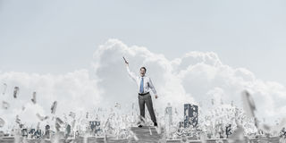 Study hard to become successful businessman. Businessman keeping hand with book up while standing among flying letters with cloudly sky on background. Mixed Stock Photos