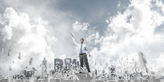 Study hard to become successful businessman. Businessman keeping hand with book up while standing among flying letters with cloudly sky on background. Mixed Stock Images