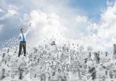 Study hard to become successful businessman. Businessman keeping hand with book up while standing among flying letters with cloudly skyscape on background Royalty Free Stock Photography