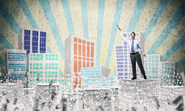 Study hard to become successful businessman. Businessman keeping hand with book up while standing among flying letters with drawn cityscape on background. Mixed Royalty Free Stock Image