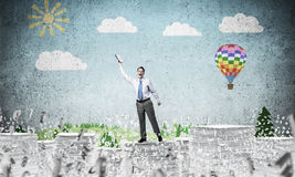 Study hard to become successful businessman. Businessman keeping hand with book up while standing among flying letters with drawn landscape on background. Mixed Royalty Free Stock Photos