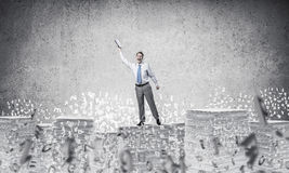 Study hard to become successful businessman. Businessman keeping hand with book up while standing among flying letters with grey background. Mixed media Stock Image