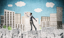Study hard to become successful businessman. Man in casual wear keeping hand with book up while standing among flying letters with drawn cityscape on background Stock Images