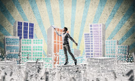 Study hard to become successful businessman. Man in casual wear keeping hand with book up while standing among flying letters with drawn cityscape on background Royalty Free Stock Photos