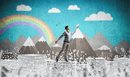 Study hard to become successful businessman. Man in casual wear keeping hand with book up while standing among flying letters with drawn landscape on background Royalty Free Stock Images