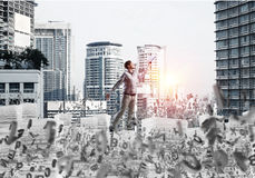 Study hard to become successful businessman. Side view of man in casual wear keeping hand with book up while standing among flying letters with cityscape and Royalty Free Stock Photography