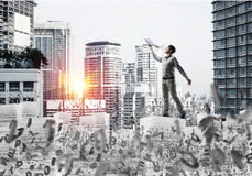 Study hard to become successful businessman. Side view of man in casual wear keeping hand with book up while standing among flying letters with cityscape and Royalty Free Stock Images