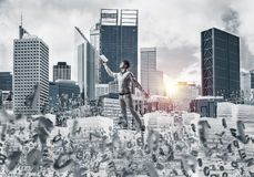 Study hard to become successful businessman. Side view of man in casual wear keeping hand with book up while standing among flying letters with cityscape and Stock Photography