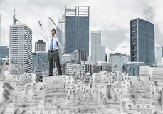Study hard to become successful businessman. Young businessman keeping hand with book up while standing among flying letters with cityscape on background. Mixed Stock Photo
