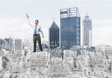 Study hard to become successful businessman. Young businessman keeping hand with book up while standing among flying letters with cityscape on background. Mixed Stock Image