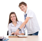 Study help. Adolescent helps colleague with her homework isolated on the white background Royalty Free Stock Photos