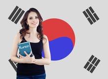 Study korean language. Happy cheerful woman student on the Republic of Korea flag background. Korean language school concept.  stock photography