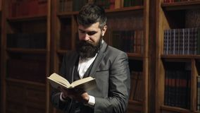 Study, learn, education, research, history, literature concept. Student stands in vintage library and holds book. Bearded man in smart suit reads near bookcase stock footage