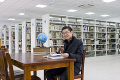 Study in a library. Young man  studys in a library with lots of  books on shelves and a computer .There is a globe on the desk. The man is smiling Royalty Free Stock Image