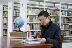 Study in a library. Young man  studys in a library with lots of  books on shelves and a computer .There is a globe on the desk Stock Photo