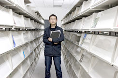 Study in a library. Young asain man  studys in a library with lots of  books on shelves Royalty Free Stock Images