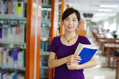 Study in a library. Young girl holds some bookes in her hand studying in a library with lots of books on shelves royalty free stock photos