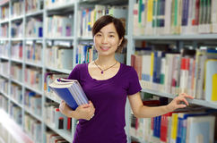 Study in a library. Young girl holds some bookes in her hand studying in a library with lots of books on shelves royalty free stock image