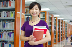 Study in a library. Young girl holds some bookes in her hand in a library with lots of books on shelves stock images