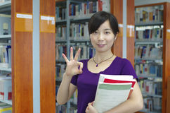 Study in a library. Young girl holds some bookes in her hand and gesture 'OK' in a library with lots of books on shelves stock image