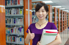 Study in a library. Young girl holds some bookes in her hand and gestures thumb up in a library with lots of books on shelves royalty free stock image