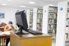 Study in a library with computer. Young students study in a library with lots of  books on shelves and a computer .The man's face was fuzzy Royalty Free Stock Photos